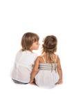 Flickor spelar, talar i ditt öra, samtalet, barns hemligheter, vita lodisar Royaltyfri Fotografi