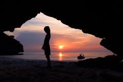Flickor står framme av en grotta på stranden Royaltyfria Bilder