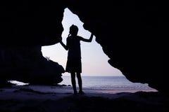 Flickor står framme av en grotta på stranden Royaltyfri Bild
