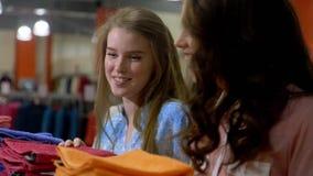 Flickor tar en blick vad I grundar Flickor väljer dräkter Diskutera känslomässigt nya saker och rabatter Flickavänner som har arkivfilmer