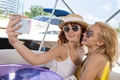Flickor tar selfie på yachten royaltyfria bilder