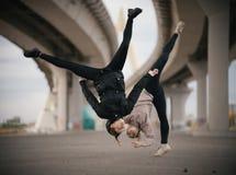 Flickor utför splittringar i luften, medan hoppa på den stads- bakgrunden av bron royaltyfri fotografi