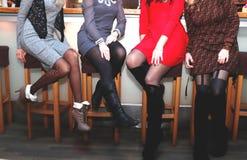 Flickor vilar på ett ungmöparti lägger benen på ryggen closeupen arkivfoton
