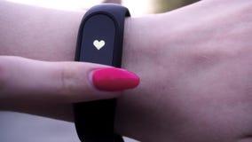 Flickorna bar ett konditionarmband Flickakontroller pulserar på konditionarmband- eller aktivitetsbogserarestegräknaren på handle stock video