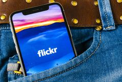 Flickr在苹果计算机iPhone x智能手机屏幕上的应用象在牛仔裤装在口袋里 Flickr app象 社会媒介象 3d网络照片回报了社交 免版税图库摄影