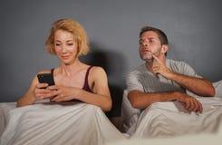 Flickvän eller fru som använder mobiltelefonen i säng och den misstänksamma frustrerade make- eller pojkvänkänslarubbningen som m royaltyfri foto