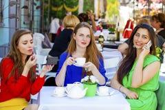 Flickvän för tre lycklig härlig flickor som dricker te i en sommar arkivfoton