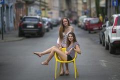 Flickvän för två unga flickor Det begreppsmässiga fotoet, en tonårig flicka sitter på en stol i mitt av gatan Arkivbild