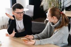 Flickvän som frågar för förklaring av hennes pojkvän som sitter på en soffa i kafét arkivbilder