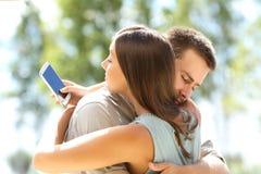 Flickvän som fuskar och kramar hennes pojkvän Arkivbilder