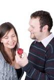 flickvän som ger stilig grabb hans present till Royaltyfri Foto