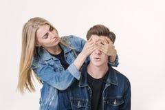 Flickvän som täcker ögonen av hennes pojkvän för en överraskning Studion sköt över vit bakgrund arkivfoto