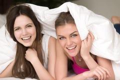 Flickvänner har gyckel på det hem- pyjamaspartiet fotografering för bildbyråer