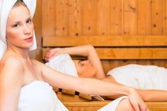 Flickvänner i wellnessbrunnsort som tycker om bastuavkoken Royaltyfri Foto