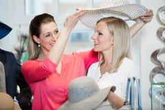 Flickvänner på shopping spree försökande damhattar och annan mode arkivbilder
