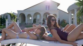 Flickvänner på sommar vilar, attraktiva vänflickor i baddräkter, och glasögon på samma tid lägger ner på dagdrivare nära stock video