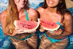 Flickvänner rymmer halva en röd vattenmelon över en blå pöl, kopplar av arkivbilder
