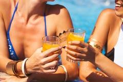 Flickvänner som klirrar exponeringsglas med coctailar på poolsidestången Fotografering för Bildbyråer