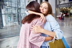 Flickvänner som möter i shoppinggalleria arkivbilder