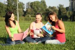Flickvänner som sitter och lärer Arkivbild