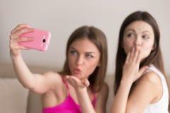 Flickvänner som tar selfie och överför luftkyssar royaltyfria foton