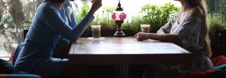 Flickvänner som tillsammans tycker om i kafé Unga kvinnor som möter i ett kafé möte av två kvinnor i ett kafé för kaffe blå klänn arkivfoto