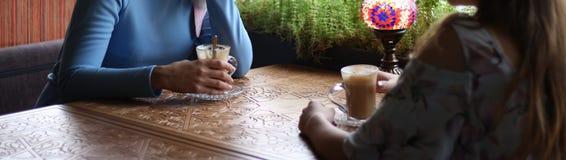 Flickvänner som tillsammans tycker om i kafé Unga kvinnor som möter i ett kafé möte av två kvinnor i ett kafé för kaffe blå klänn arkivbilder
