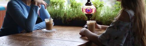 Flickvänner som tillsammans tycker om i kafé Unga kvinnor som möter i ett kafé möte av två kvinnor i ett kafé för kaffe blå klänn royaltyfri bild
