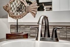 Fließendes Wasser vom Spitzenbadezimmer-Hahn Stockfotos