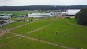 Flie della gente un aquilone su erba nel giorno di estate Bambini del gruppo che pilotano aquilone all'aperto Aquilone di volo ne stock footage