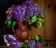 Flieder in einem keramischen Vase, in einem Buch und in einer Stunde auf dem Tisch stockfotografie
