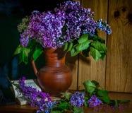 Flieder in einem keramischen Vase, in einem Buch und in einer Stunde auf dem Tisch lizenzfreie stockbilder