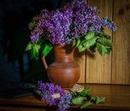 Flieder in einem keramischen Vase und in einer Stunde auf dem Tisch lizenzfreies stockbild