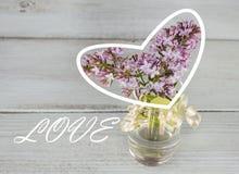 Flieder in einem transparenten Vase auf einem hölzernen Hintergrund, weißes Herz und die Aufschrift lieben Lizenzfreie Stockbilder