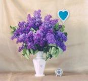 Flieder in einem Vase und in einem kleinen Herz-förmigen Spiegel Lizenzfreie Stockfotos