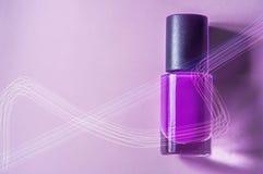 Flieder, purpurroter Lack in einer Flasche mit einem schwarzen Deckel, im hellen Licht, auf einem purpurroten, rosa Hintergrund Stockbild