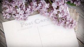 Flieder und Postkarte auf verwittertem Holz Lizenzfreie Stockfotos