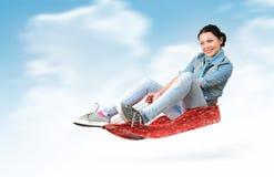Fliege des jungen Mädchens auf einem Schlitten im Schnee Lizenzfreie Stockfotografie