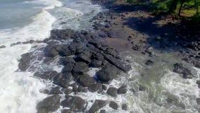 Fliege um die schwarzen Felsen, die Wellen an Soka-Strand, Bali-Insel zerschmettern stock video