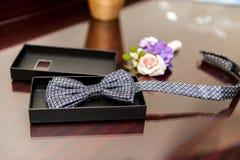 Fliege und Blumenverzierung für Bräutigam auf Holztisch stockfotografie