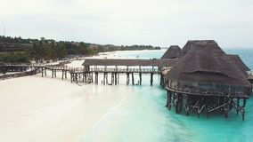 Fliegen über afrikanisches Holzhaus mit Pier auf Stelzen mit Strohdach stock footage