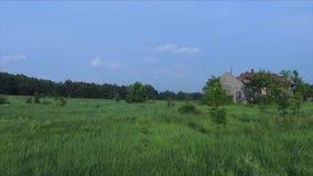 Fliegen über dem Gras und dem verlassenen Haus stock footage