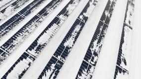 Fliegen über den Bauernhofsonnenkollektoren im Winter nach dem Wirbelsturm Platten unter dem Schnee stock footage