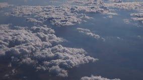 Fliegen über der Schicht von Wolken und von Schauen auf Landschaft durch die Wolken stock footage