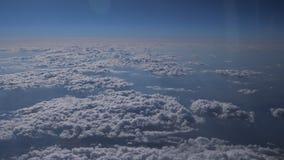 Fliegen über der Schicht von Wolken und von Schauen auf Landschaft durch die Wolken stock video footage