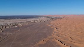Fliegen über eine Wüsten-Düne nahe Dorf Merzouga in Marokko mit Brummen von oben (von der Luft) stock video
