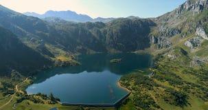 Fliegen über einen See zwischen Berge und mit wenig Wege arround es stock video footage