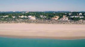 Fliegen über Feriendorf auf Ufer-Ozean stock footage