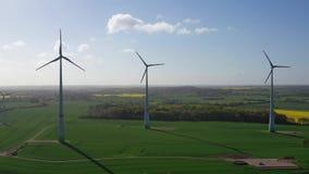 Fliegen über grünen Feldern mit Windkraftanlagen stock video footage