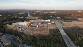 Fliegen über neuem Mallbau nahe bei Eigentumswohnungen und Landstraße in Atlanta-Vororten stock video footage